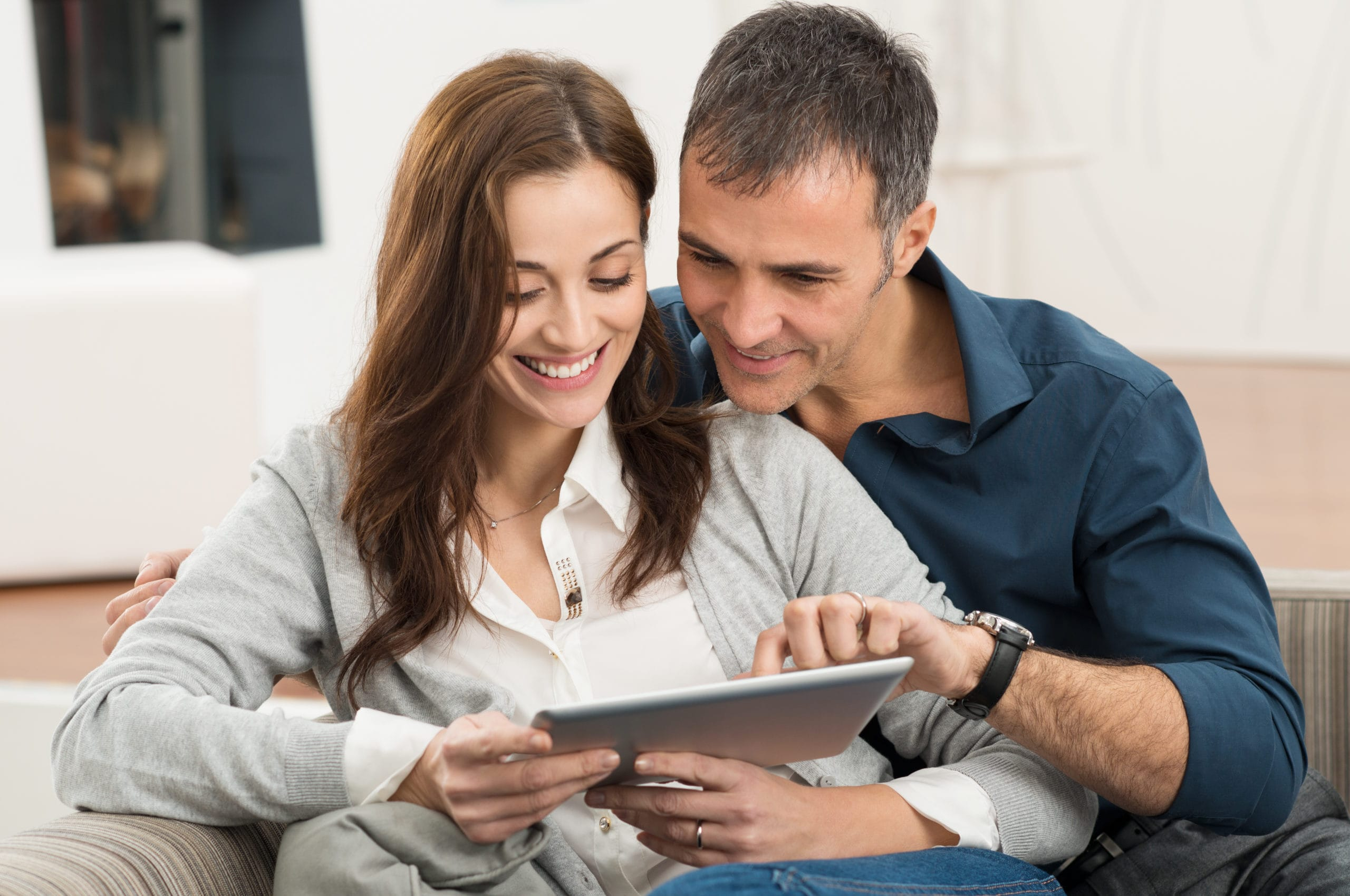 Portrait Of Happy Couple Sitting On Couch At Home Using Digital Tablet